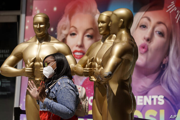 Nikki Slaughter of Tampa Bay, Fla., poses for a photo near fake Oscar statues on Hollywood Blvd., Thursday, April 15, 2021, in…
