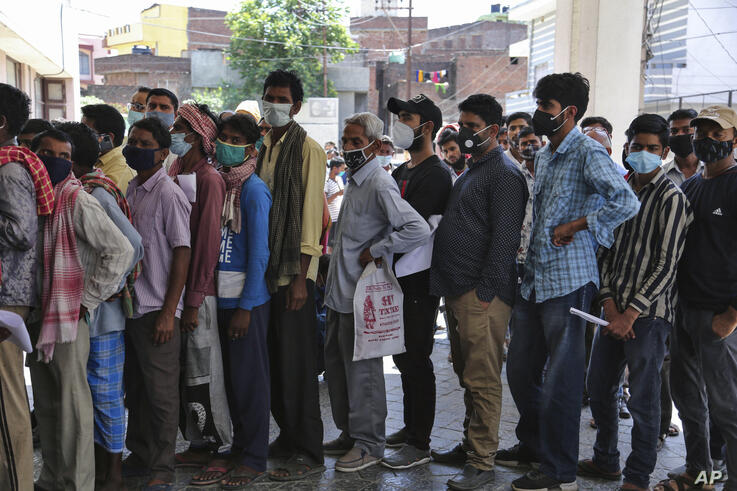 FILE- In this April 19, 2021 file photo, people wearing face masks as a precaution against the coronavirus line up without any…