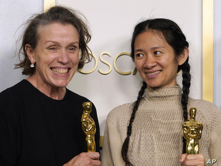 """Producers Frances McDormand, left, and Chloe Zhao, winners of the award for best picture for """"Nomadland,"""" pose in the press…"""