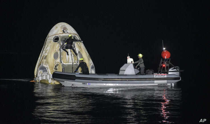 Support teams work around the SpaceX Crew Dragon Resilience spacecraft shortly after it landed with NASA astronauts Mike…