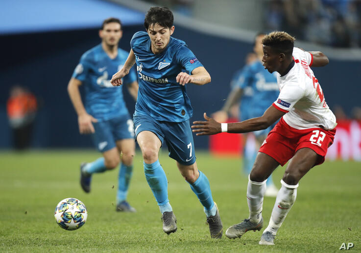 Zenit's Sardar Azmoun, left, fights for the ball with Leipzig's Nordi Mukiele during the Champions League group G soccer match…
