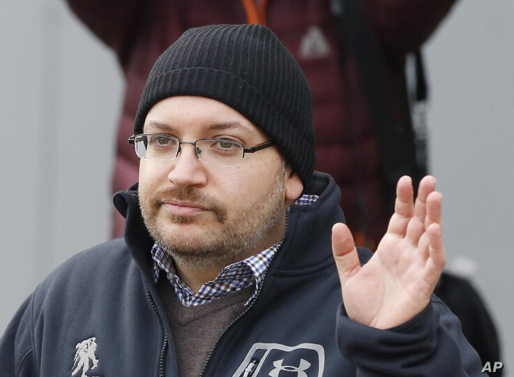 FILE - In this Jan.20, 2016 file photo, U.S. journalist Jason Rezaian waves as he poses for media people in front of Landstuhl…