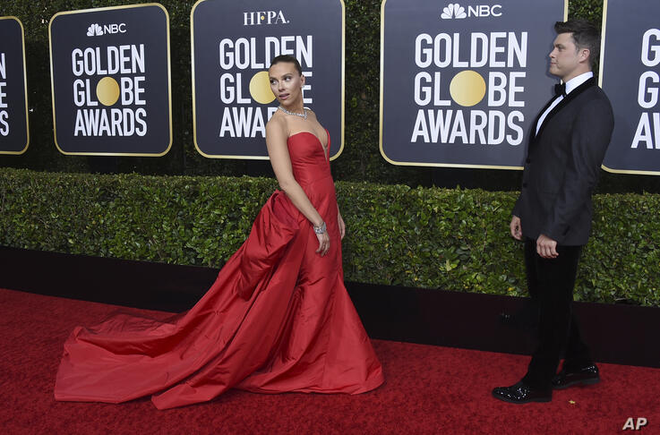 Scarlett Johansson, left, arrives as Colin Jost looks on at the 77th annual Golden Globe Awards at the Beverly Hilton Hotel on…
