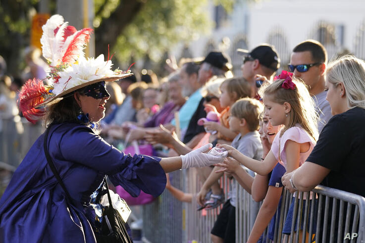 """A woman dressed in period costume hands a trinket to a child during a parade dubbed """"Tardy Gras,"""" to compensate for a cancelled…"""