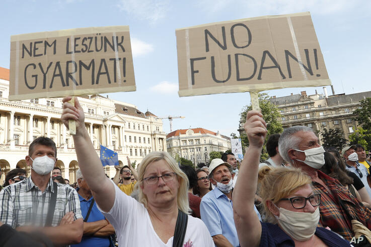 Protesters hold placards reading in Hungarian 'we will not be a colony', left, and 'no Fudan' as they gather in downtown…