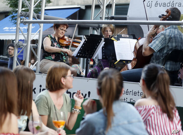 Members of the Budapest Festival Orchestra play music on the back of a truck while driving through downtown Budapest, Hungary,…