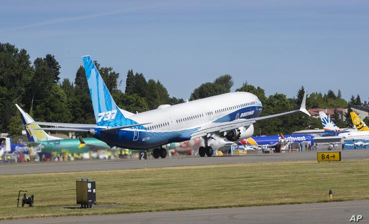 The final version of the 737 MAX, the MAX 10, passes other 737 MAX planes as it takes off from Renton Airport in Renton, Wash.,…