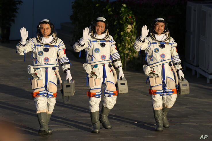 Chinese astronauts, from left, Tang Hongbo, Nie Haisheng, and Liu Boming wave as they prepare to board for liftoff at the…