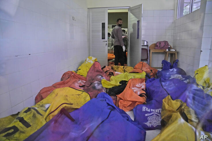 A police officer stands near body bags containing the bodies of the victims of a prison fire at the local hospital's morgue in…