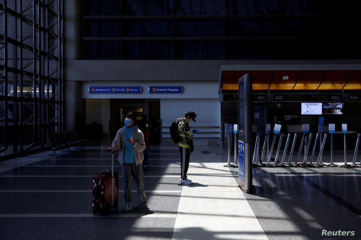FILE PHOTO: Passengers wear protective face masks at Los Angeles International Airport (LAX) on an unusually empty Memorial Day weekend during the outbreak of the coronavirus disease (COVID-19) in Los Angeles