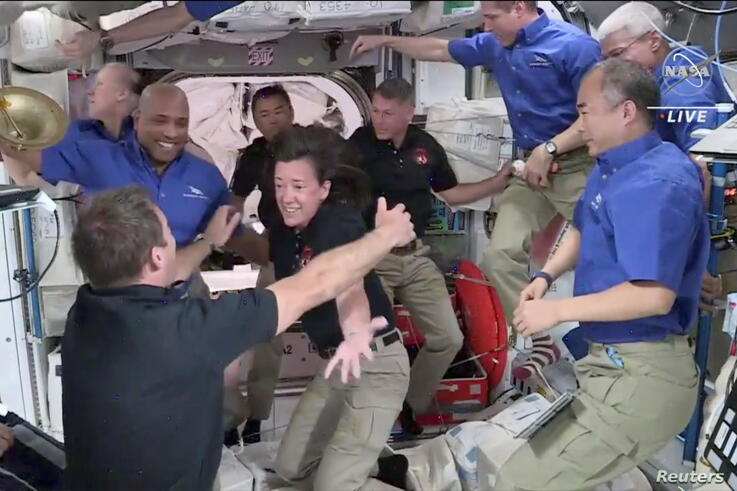 Crew ۲ is welcomed by Crew ۱ aboard the International Space Station