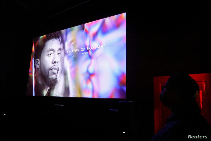 An audience member watches as Chadwick Boseman appears on screen during the annual In Memoriam presentation, at an Oscars watch party at the Stuart & Cinema Cafe, in Brooklyn