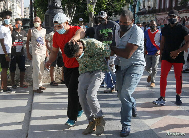 Plain clothes police detain a person during protests against and in support of the government, in Havana