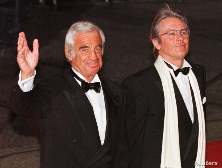 FILE PHOTO: French actors Jean-Paul Belmondo and Alain Delon pose for photographers as they arrive at Berlin's theatre