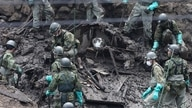 Members of Japan's Self-Defence Forces search for missing people at the scene of a landslide following days of heavy rain in…