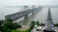 FILE - In this Sept. 9, 2017, file photo, visitors walk across the Yalu River Broken Bridge, right, next to the Friendship…
