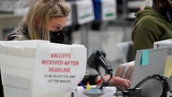 Officials work on ballots at the Gwinnett County Voter Registration and Elections Headquarters, Friday, Nov. 6, 2020, in…