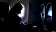 A passenger wears a face mask she travels on a Delta Airlines flight Wednesday, Feb. 3, 2021, after taking off from Hartsfield…