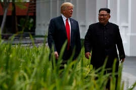 FILE - President Donald Trump walks with North Korean leader Kim Jong Un on Sentosa Island, June 12, 2018, in Singapore.