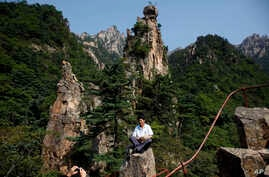FILE - A North Korean guide poses for photos among the peaks of the Mount Kumgang resort, also known as Diamond Mountain, in North Korea, Sept. 1, 2011. South Korea's Moon Jae-in is look at ways to build relations with North Korea, including resuming t...