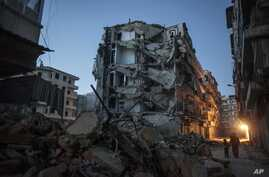 Residents walk past buildings damaged in heavy fighting between Free Syrian Army fighters and government forces in Aleppo, Syria, December 2, 2012.