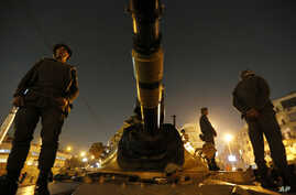 Soldiers stand guard on top of a tank in front of the presidential palace in Cairo, Egypt, December 9, 2012.