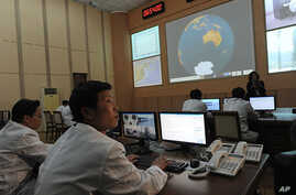 North Korean technicians work at the control room of the Tongchang-ri space center on April 8, 2012.  (AFP photo)