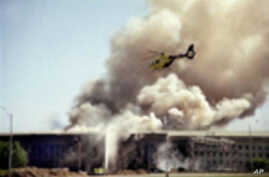 A helicopter flies over the Pentagon in Washington, Tuesday, Sept. 11, 2001 as smoke billows over the building. The Pentagon took a direct, devastating hit from an aircraft and the enduring symbols of American power were evacuated as an apparent terrorist