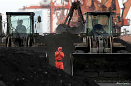 FILE - An employee walks between front-end loaders used to move coal imported from North Korea at Dandong port in the Chinese border city of Dandong, Dec. 7, 2010.