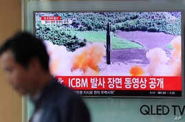 A man walks past a TV screen showing a local news program about North Korea's reported firing of an ICBM, at Seoul Train Station in Seoul, South Korea, July 5, 2017.