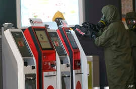 FILE - A hazmat crew scan the check-in kiosk machines at Kuala Lumpur International Airport 2 in Sepang, Malaysia, Feb. 26, 2017. Malaysian police ordered a sweep of Kuala Lumpur airport for toxic chemicals and other hazardous substances following the ...