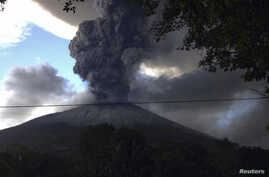 The Chaparrastique volcano, behind electricity cables, spews ash at the municipality of San Miguel December 29, 2013. The Chaparrastique volcano in eastern El Salvador belched a column of hot ash high into the air on Sunday, frightening nearby residents a