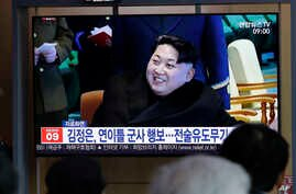 """FILE - People watch a TV news program reporting about North Korea's test-fire of a """"new-type tactical guided weapon,"""" with a file footage of North Korean leader Kim Jong Un, at the Seoul Railway Station in Seoul, South Korea, April 18, 2019."""