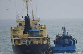 FILE - This photo released by Japan's Ministry of Defense shows what it says is the North Korean-flagged tanker Yu Jong 2, left, and Min Ning De You 078 lying alongside in the East China Sea, Feb. 16, 2018.