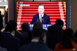 People watch a TV screen showing the live broadcast of South Korean President Moon Jae-in's New Year's speech at the Seoul Railway Station in Seoul, South Korea, Tuesday, Jan. 7, 2020. Moon said he hopes to see North Korean leader Kim Jong Un…
