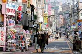 A couple wearing masks to protect against contracting the coronavirus disease (COVID-19) walk along a street in Seoul, South…