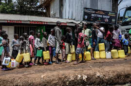 Children queue with their jerrycans to fill them with free water distributed by the Kenyan government at Kibera slum in Nairobi…