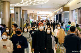 People wear masks to avoid the spread of the coronavirus disease (COVID-19) at a department store in Seoul, South Korea April…