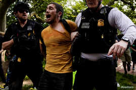 A protestor yells as he is detained by U.S. Secret Service uniformed division officers as demonstrators march to the White…
