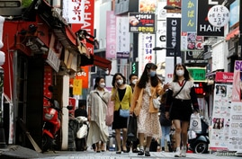 People wearing masks walk at Myeongdong shopping district amid social distancing measures to avoid the spread of the…