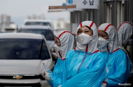 FILE PHOTO: Medical staff in protective gear work at a 'drive-thru' testing center for the novel coronavirus disease of COVID…