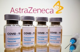 "FILE PHOTO: Vials with a sticker reading, ""COVID-19 / Coronavirus vaccine / Injection only"" and a medical syringe are seen in…"