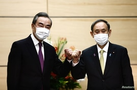 Japan's Prime Minister Yoshihide Suga (R) bumps elbows with China's State Councillor and Foreign Minister Wang Yi at the start…