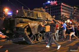 FILE PHOTO: People react near a military vehicle during an attempted coup in Ankara, Turkey, July 16, 2016.     REUTERS/Tumay…