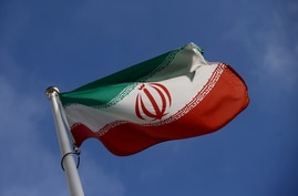 FILE PHOTO: The Iranian flag waves in front of the International Atomic Energy Agency (IAEA) headquarters, before the beginning…