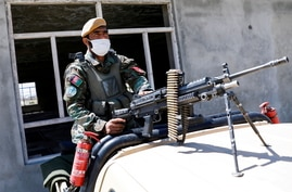 FILE PHOTO: An Afghan National Army soldier sits on a back of an army vehicle at a checkpoint on the outskirts of Kabul,…