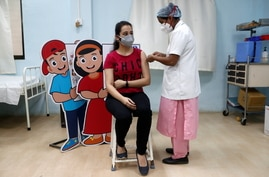 A woman receives a dose of COVISHIELD, a coronavirus disease (COVID-19) vaccine manufactured by Serum Institute of India, at a…