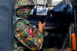 FILE PHOTO: A soldier uses a mobile phone as he sit inside a military vehicle outside Myanmar's Central Bank during a protest…