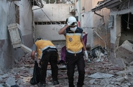 Members of Syria's Civil Defence service (White Helmets) sift through the rubble at Al-Shifaa hospital following shelling of…