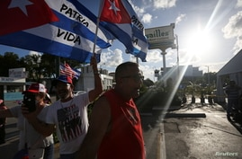 Emigres wave Cuban flags outside Versailles restaurant, in reaction to reports of protests in Cuba against its deteriorating…